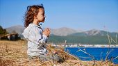 Cute Little Child Gurl Meditating Alone In Lotus Pose At Lake Shore poster
