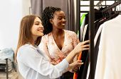 Personal Stylist. Shopping Assistant Choosing Trendy Clothes For Female Client In Fashion Store. poster
