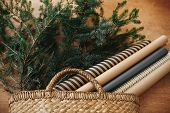 Rustic Basket With Fir Branches And Festive Wrapping Paper On Rustic Wooden Background. Winter Holid poster