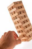 stock photo of jenga  - Piece pulled out from tower made of wooden blocks - JPG