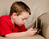 stock photo of couch potato  - Couch potato concept of boy playing video game while resting on sofa - JPG