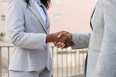 Agent And Customer Meeting Outside. Business Man And Black Woman In Office Suits Standing Outside An poster