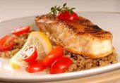stock photo of halibut  - Fresh halibut seared with tomato lemon and thyme on a bed of brown rice - JPG