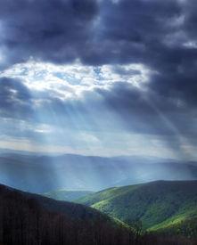 stock photo of sun rays  - Bright sun rays shining through stormy clouds - JPG