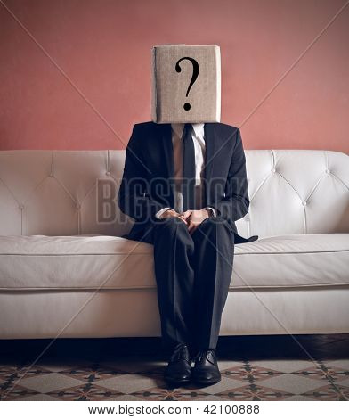 businessman sitting on sofa with head in box