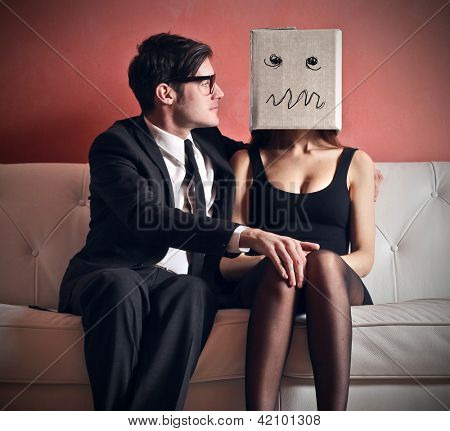 man embraces beautiful woman with a box on her head sitting on the couch