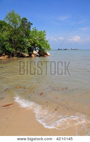 Sandy Beach With Waves And Blue Sky
