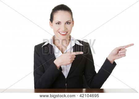 Business woman sitting at the desk pointing with finger to empty copy space, isolated over white background