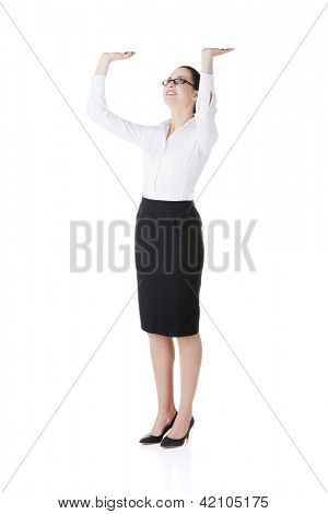 Smiling young business woman is holding something abstract above her head. Happy girl with raised hands. Isolated on white background.
