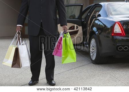 Chauffeur holding shopping bags by luxury car