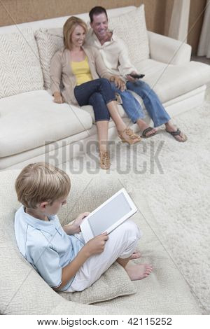 Little boy holding digital tablet with his parents watching TV at home