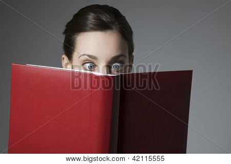 Astonished young woman reading book with eyes wide open