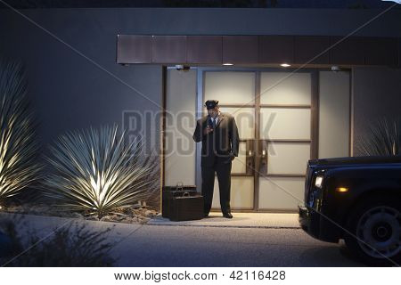 Chauffeur standing at doorway with luggage bags at night