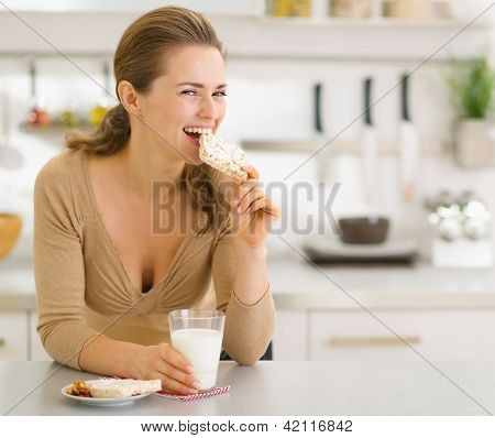 Young Woman Eating Snacks In Modern Kitchen