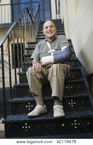 Low  view of elderly man with broken arm sitting on stairs
