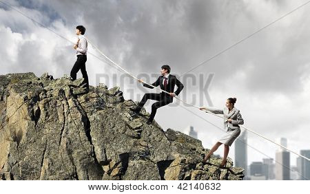 Image of three businesspeople pulling rope atop of mountain