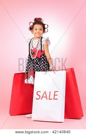 Portrait of a cute little pin-up girl with sale bags standing over pink background.