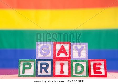 Blocks spelling gay pride on rainbow background
