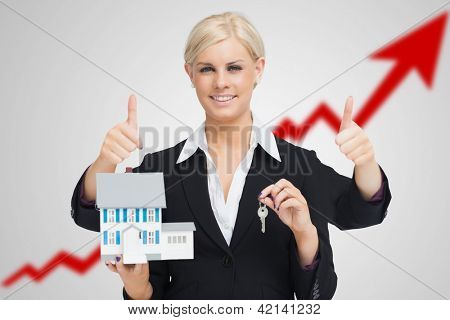 Multi-tasking estate agent holding keys and model house while giving thumbs up against red growth arrow