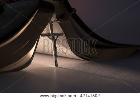 Crucifix from rosary beads propping open the bible