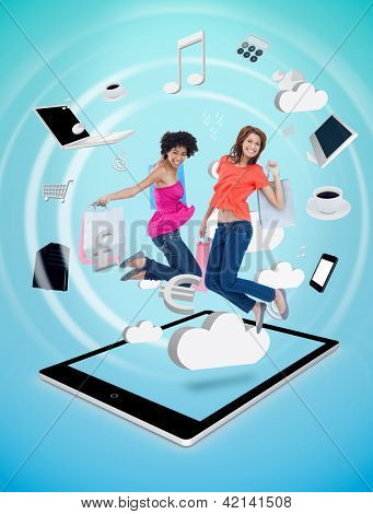 Two cute women jumping on a tablet pc against a digital blue background