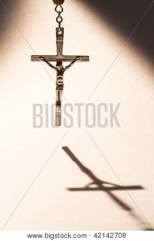 Cross hanging from rosary beads casting a shadow