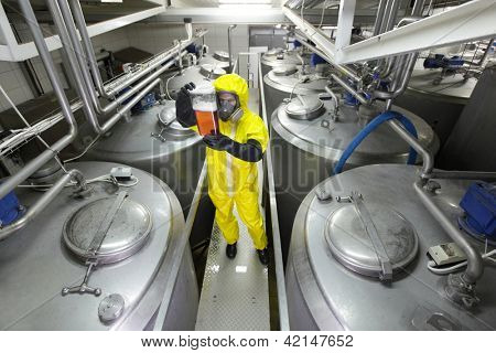 industrial professional , in protective uniform,mask,goggles,gloves and wellies checking sample in plastic container