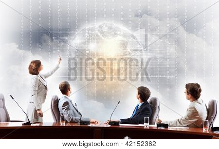 Image of businesspeople at presentation looking at virtual project.Elements of this image are furnished by NASA