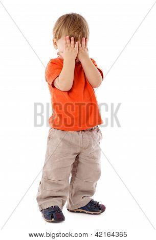 Niño ocultar el rostro bajo las manos