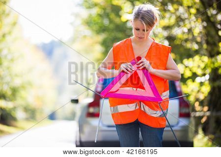 Young female driver wearing a high visibility vest, setting up the reflective trianglec after her car has broken down