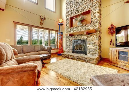 Living Room With High Ceiling, Stone Fireplace And Leather Sofa.