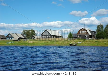 Northern Russian Village At The Lake Bank