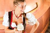 Woman in Bavarian Tracht, a female brewer, with beer stein in brewery
