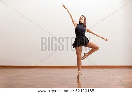 Happy ballet dancer in a studio