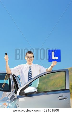 Happy man posing near his car, holding a L sign and car key after having his driver's licence on a road