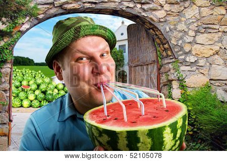 Cheerful farmer drinking watermelon juice through a tubules