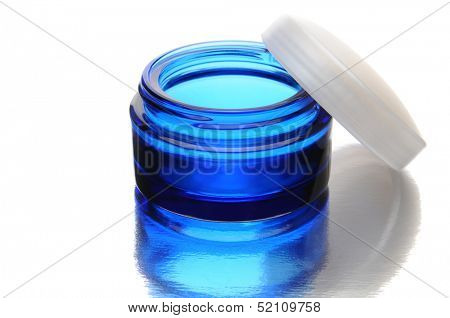 Closeup of a blue jar with its lid leaning on it's right side. Horizontal format over white with reflection.
