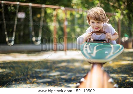 Happy child playing seesawing in playground