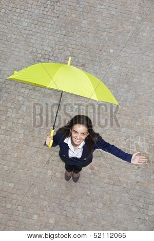 Smiling young business woman with yellow umbrella checking if it's raining