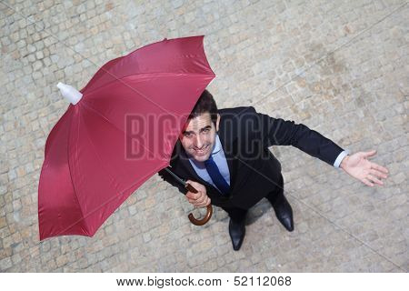 Confident businessman with umbrella checking if it's raining