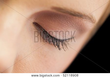 Close up on eye wearing eye liner and natural eye shadow on black background