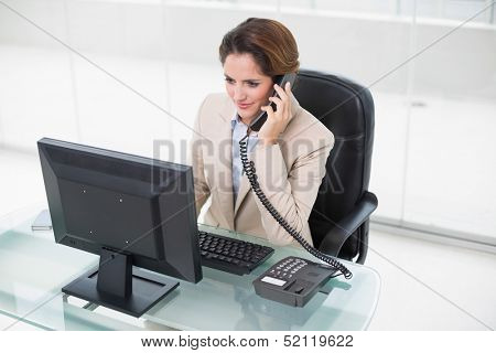 Brunette businesswoman using phone and looking at computer in bright office