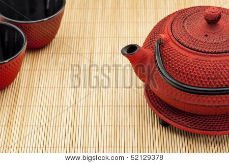 Japanese tetsubin and tea cups on a bamboo mat - a traditional cast iron red hobnail design with black enamel inside
