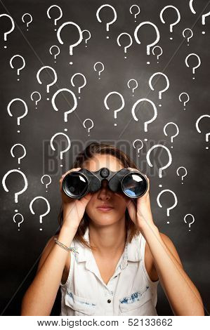 young woman using binoculars in front of chalkboard with interrogation symbols