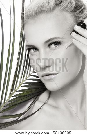 Duotone portrait of young fresh beautiful healthy woman applying serum on her face