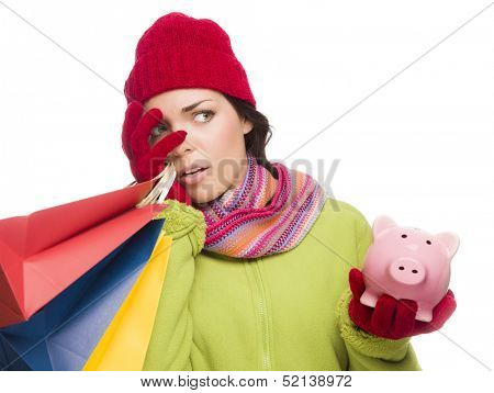Concerned Expressive Mixed Race Woman Wearing Winter Clothing Holding Shopping Bags and Piggy Bank Isolated on White Background.