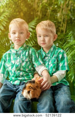 Image of cute young twins posing with guinea pig