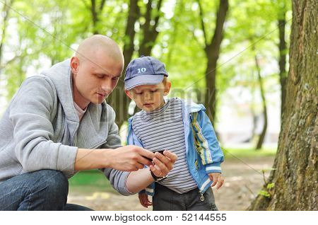 Baby With Interest Looking At Daddy Phone In Park