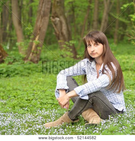 Beautiful Young Woman Sits On A Grass In Park