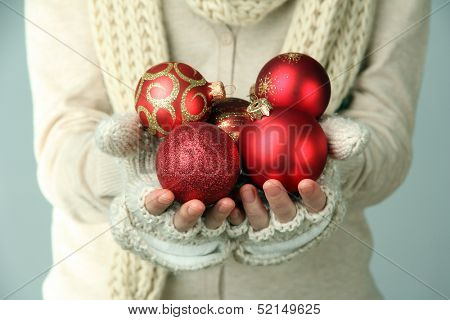 Female hands  in mittens Christmas tree balls, on color background